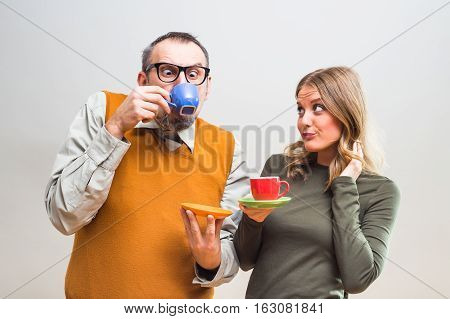 Funny nerdy man and beautiful woman enjoy drinking coffee.