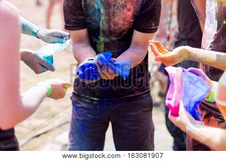 Young people taking colorful powder to throw it in the air during Holifest