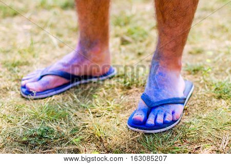 Body parts.Close-up shooting of guy's feet wearing blue flip-flops stained with colorful powder