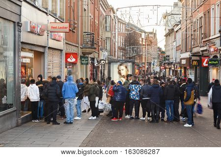 NOTTINGHAM ENGLAND - DECEMBER 26: Boxing Day sale shoppers queue outside Footlocker sports store on Clumber Street. In Nottingham England. On 26th December 2016.