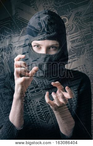 hacker girl in balaclava curled fingers makes cyber attack through the background of the silhouette circuit board.