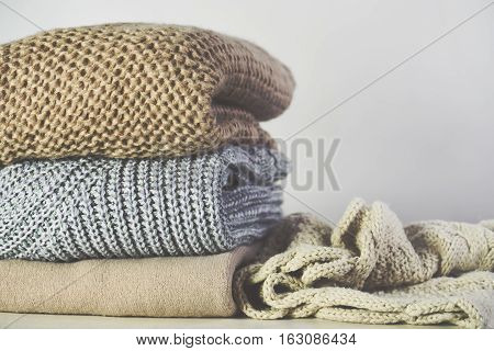 tinted image warm sweaters are stacked on the table on a light grey background horizontal
