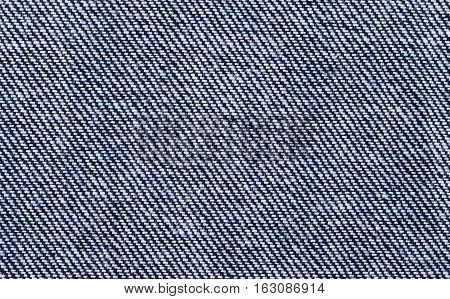 Blue denim textile macro photo. Surface of sturdy cotton warp-faced fabric. Twill, type of textile weave with pattern of diagonal parallel ribs. Warp thread is dyed indigo, weft thread is left white.