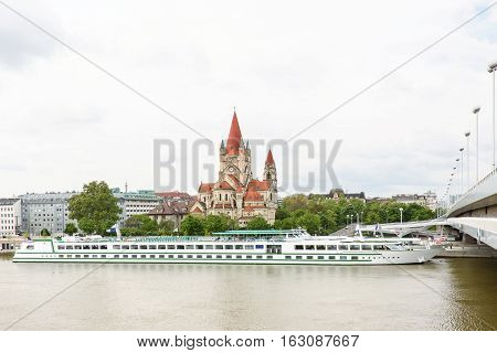 Church heiliger franz of assisi at mexikoplatz on danube river and a boat, vienna, austria