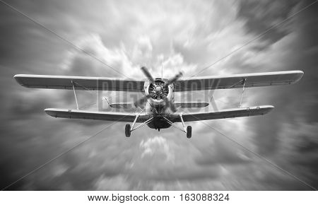 Biplane landing with cloudy sky on the background. Black and white