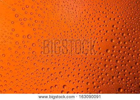 misted glass of beer close up of an orange bright background