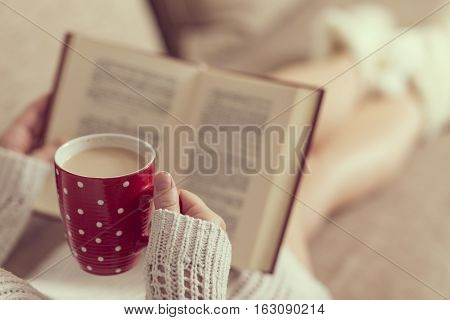 Young woman lying on the living room sofa reading a book and holding a cup of hot coffee. Selective focus