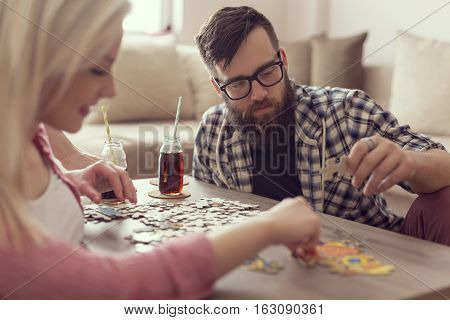Couple in love sitting on the floor next to a table solving a jigsaw puzzle problem and enjoying their leisure time activities.