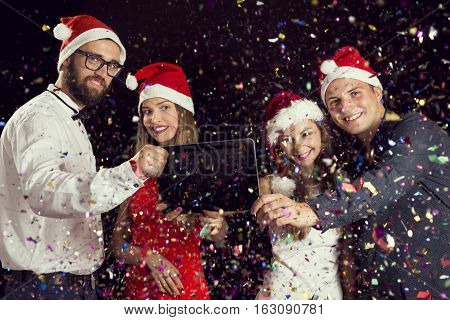 Two beautiful young couples wearing Santa's hats and taking a midnight selfie at a New Year's Eve party