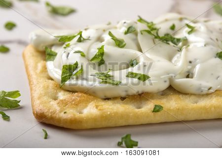 Close up of thin crispy crackers with cream cheese and parsley