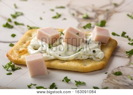 Thin crispy crackers with cream cheese ham and parsley