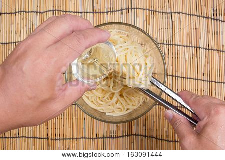 cooking oil to Spaghetti with tongs / cooking spicy spaghetti concept