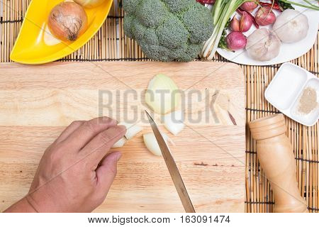 Chef slicing onion on wooden broad / cooking spicy spaghetti concept