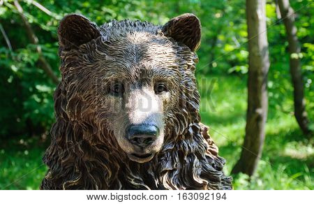 Carved wooden bear head in park at sunny summer day