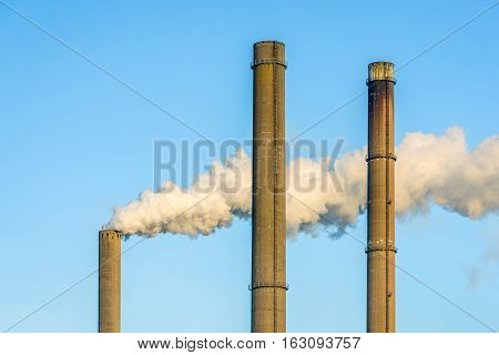 Gray and dirty smoke from a high concrete chimney of a power station contrasting with a bright blue sky on a sunny day in the winter season. Two other chimneys are out of use.