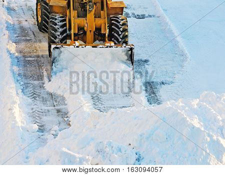 Snow drifts. Tractor clears the way after heavy snowfall.