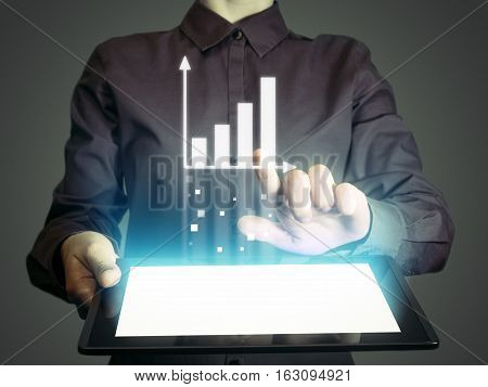 Image of a girl with a tablet in hands. She presenting a financial analysis using chart.Concept internet for business analytics.