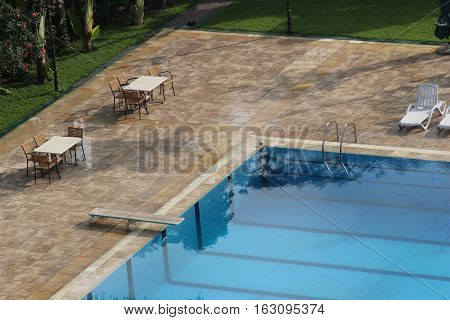 A swimming pool with tables and chairs around