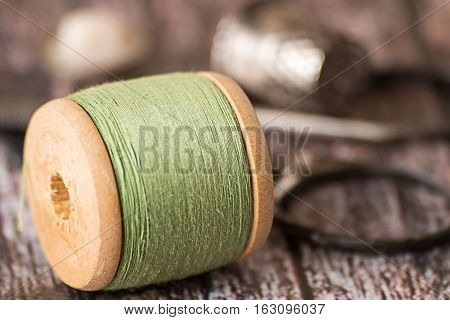 Old wooden coil with sewing thread, scissors and thimble on a wooden background.