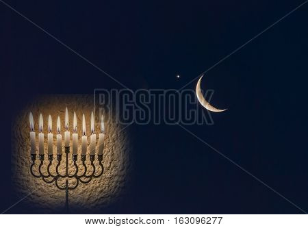 Low key composite image with menorah with glitter lights of burning candles and crescent moon on nocturnal black sky. Image symbolizes Jewish holiday of Hanukkah