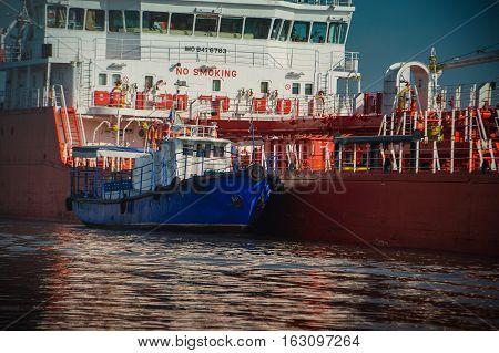Blue Tugboat Assisting A Large Oil Tanker.