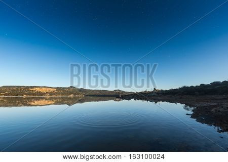 Ripples On A Lake At Sunrise With Star Filled Deep Blue Sky