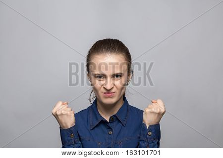 Portrait of angry woman on gray background