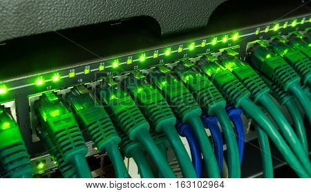 Network switch and green ethernet cables glowing in server room. Patch cords connected to router in data center. Horizontal technology background