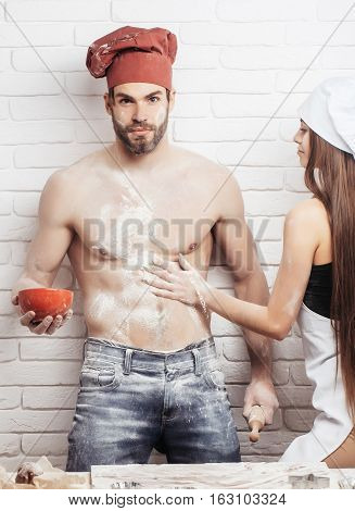 Pretty girl or beautiful woman cute helper sprinkles flour on handsome man or muscular chef cook baker with sexy muscle torso body with six packs and abs on kitchen wall