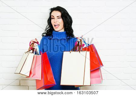 Pretty girl or beautiful winking woman young cute sexy female model with long brunette hair and red lips holds shopping bags on white background in blue dress