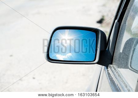 car rear-view mirror with a reflection of the sun