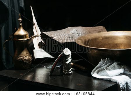 Female hand pours water from jug to copper basin. Vintage barber or shaver tools on wooden table. Old razors with blades scissors axe brush and towel in barbershop or hairdressing saloon