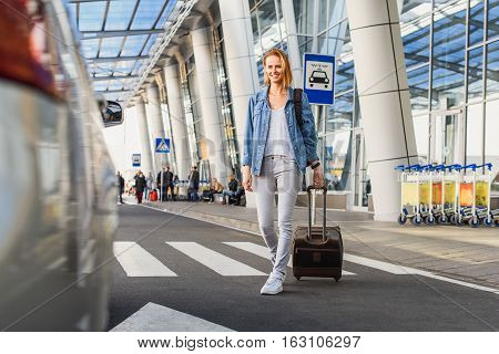 Cheerful young woman is going to taxi from the airport. She is carrying suitcase and smiling