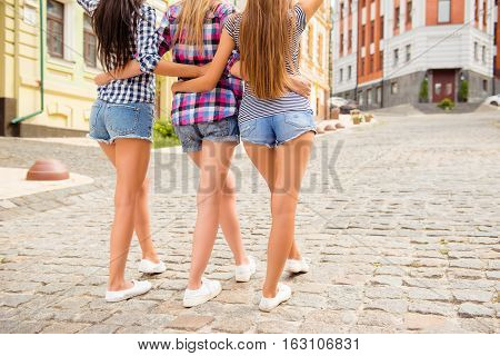 Back View Of Three Shapely Girls Huging And Walking In The City