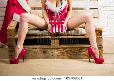 christmas female sexy legs of pretty woman in red santa claus bodysuit and shoes with present or gift new year box for xmas with coat on wood bench