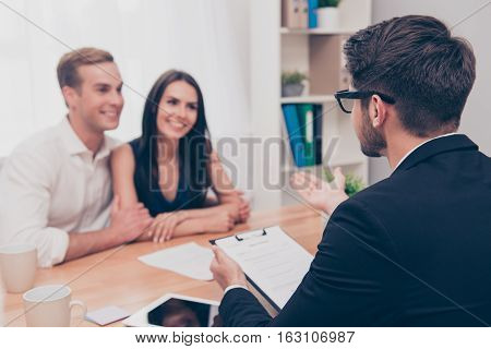 Happy young family working with real estate agent