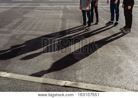 Close of male legs standing at airport outdoors. Friends are waiting for flight. Focus on their shadows