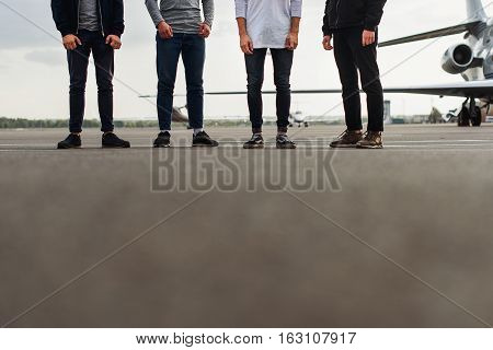 Close up of men legs standing on airfield near plane. Low angle of road