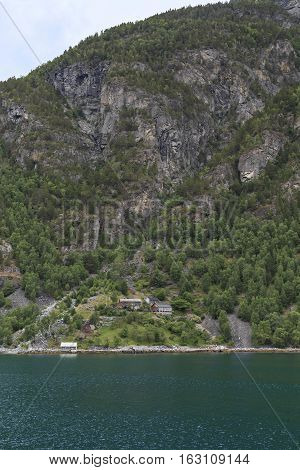 GEIRANGERFJORD, NORWAY - JULY 6, 2016: This is single home on the shore of the fjord which are used mainly for summer holidays in the countryside.
