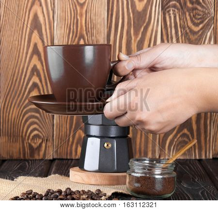 Moka coffee pot. Metal italian espresso maker with cup on wood board
