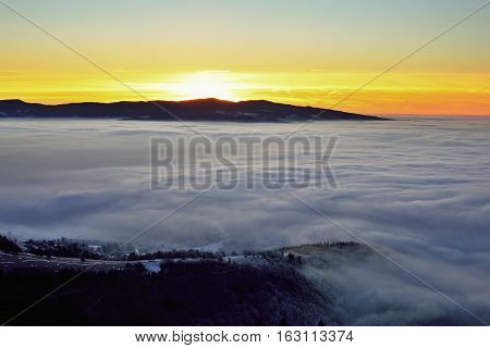 Landscape with trees and fog. Winter inversion in Slovakia. Freeze land. Low sky scenery at sunrise.