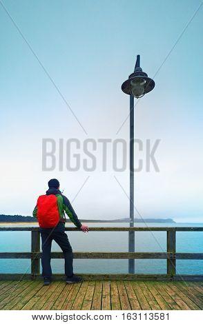 Man In Autumn Mist On Pier Above Sea. Depression, Dark  Atmosphere. Mole, Wet Board Above Sea.