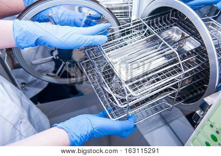 Dentist assistant's hands get out sterilizing medical instruments from autoclave. Selective focus poster