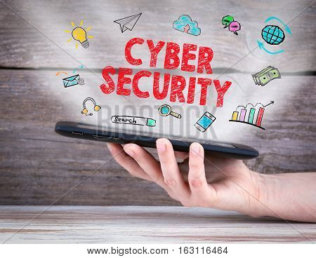 Cyber Security concept. Tablet computer in the hand. Old wooden background.