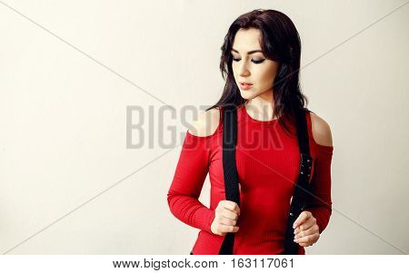 A beautiful young teenager girl in a red sweater and black suspender standing isolate for white background.