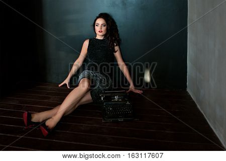 portrait pf young brunette woman writer with old machine