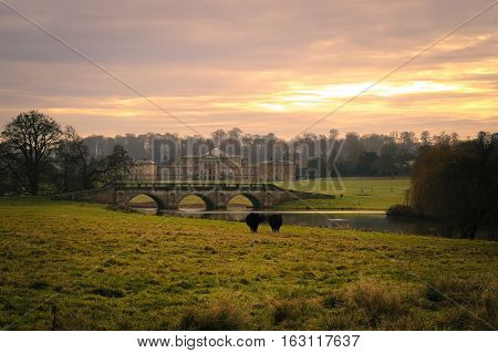 Sunset view of hall a bridge at Kedleston Hall