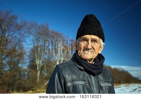Old man outdoor in the winter closeup portrait