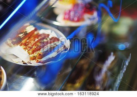 Delicious sweet custard cream cakes on a tray in the window on a beautiful blurred background with reflection