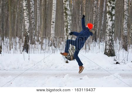 A young active person athletic jump and swing her arms while Jogging on a birch grove in winter.